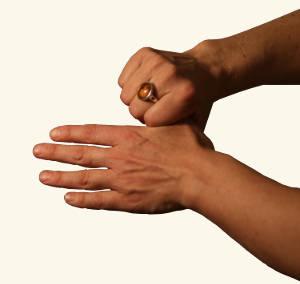 Eine Hand umfasst den Daumen der anderen Hand.