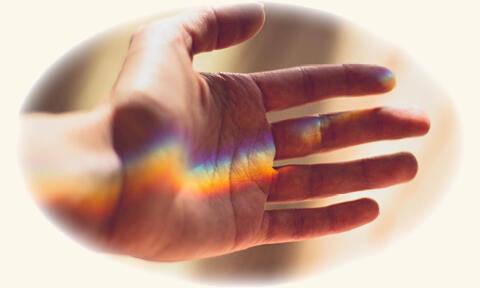 Auf der Innenseite einer Hand leuchten die Farben des Regenbogens.