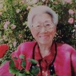 Porträt Mary Burmeister, eine ältere Frau mit Brille und rosa Jacke steht vor einem Rosenstrauch und lächelt in die Kamera.